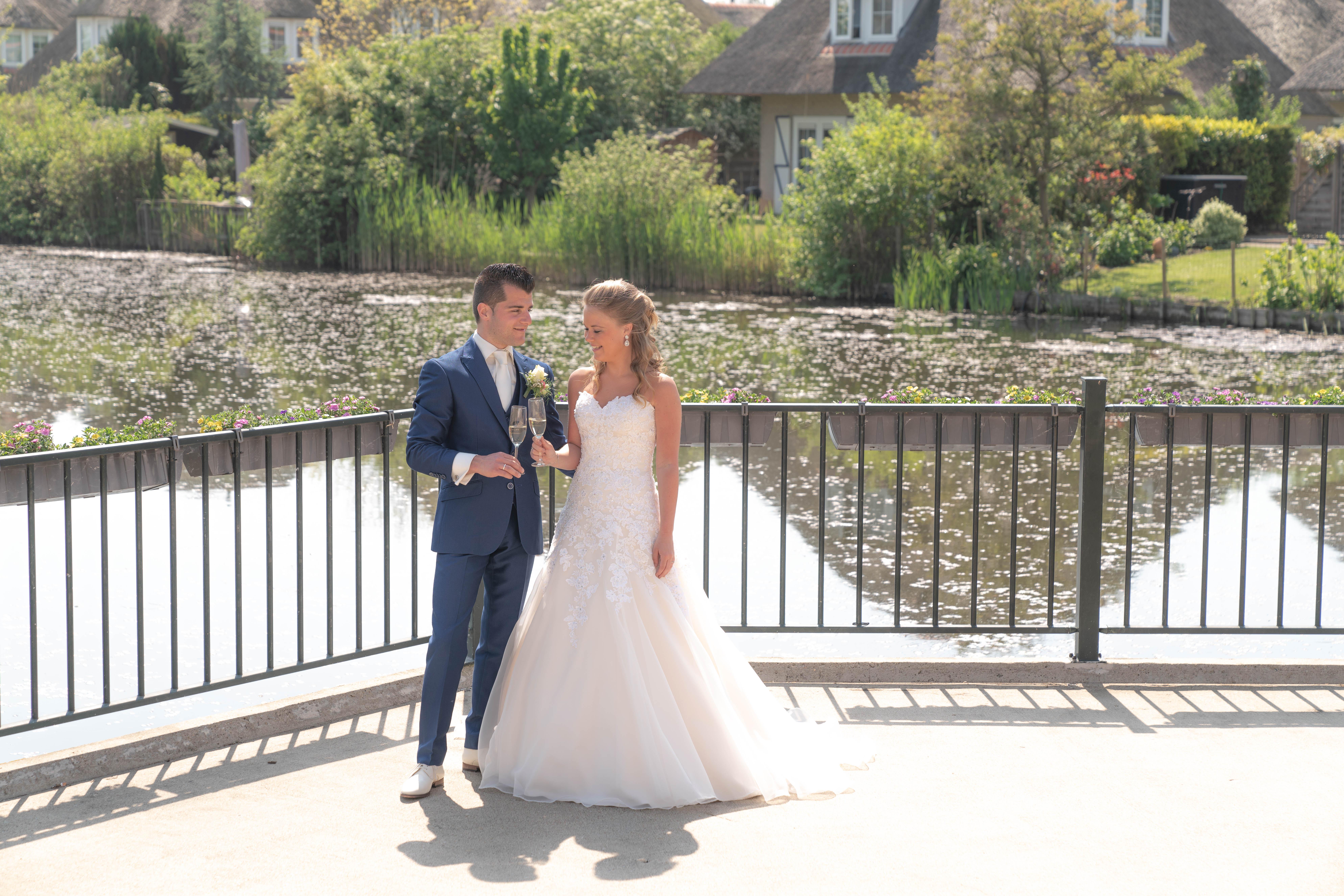 Bruidspaar dat proost op hun bruiloft bij langs een vijver