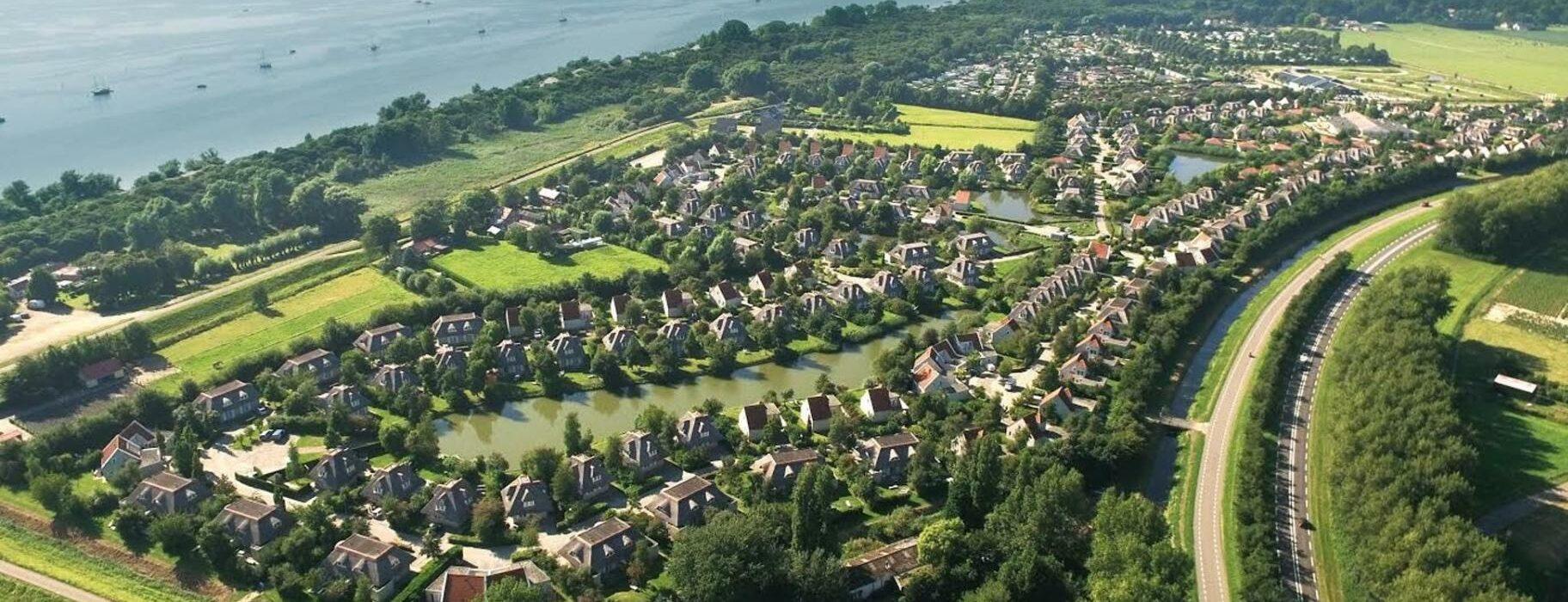 Drone foto van resort città romana met veel groen en water op de achtergrond